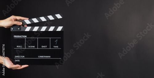 Canvas Print Hand is holding Black clapperboard or movie slate on black background