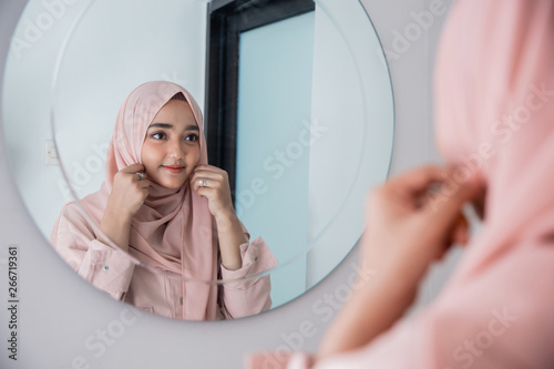 Fotografia  muslim woman fix and make up her self looking at the mirror