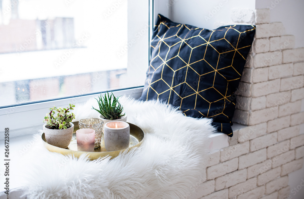 Fototapety, obrazy: Cozy real home decoration, burning candles on golden tray with pillow on white faux fur on windowsill
