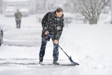 Man In Winter Coat Cleaning Shoveling Driveway Street In Heavy Snow Storm With Shovel And Abstract Blurry Blurred Snowflakes Falling