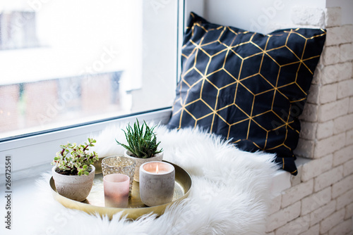 Obraz na plátně  Cozy real home decoration, burning candles on golden tray with pillow on white f