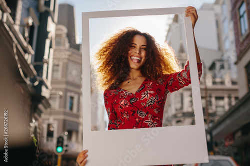 Obraz Funny young woman with a blank photo frame - fototapety do salonu