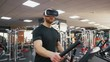 Young strong man exercising on treadmill at the gym, wearing VR glasses
