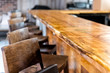 Row of empty wooden vintage bar stools by counter in drink establishment pub during day closeup of retro wood and nobody