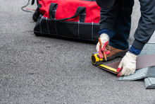 Closeup Of Construction Man Measuring Roof Shingles With Tape On Asphalt Ground Driveway Street