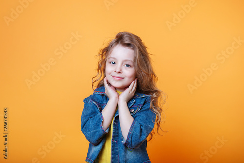 Studio portrait of smiling little girl on a yellow background
