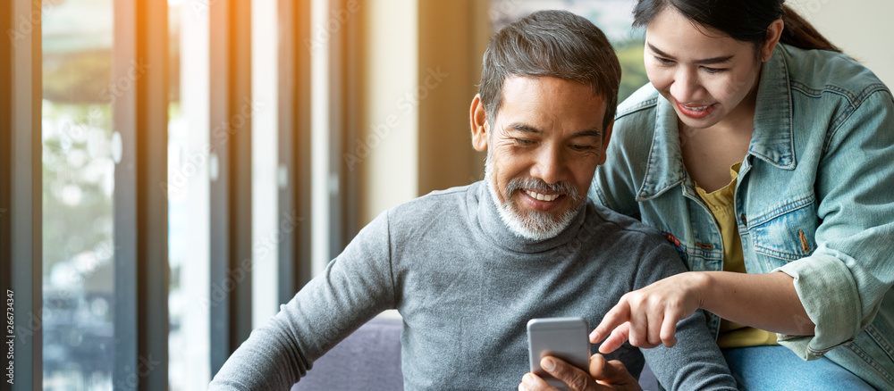 Fototapeta Smile attractive stylish short beard mature asian man using smartphone with young woman. Daughter teach asian old man or dad using internet social media network technology with digital gadget at home.