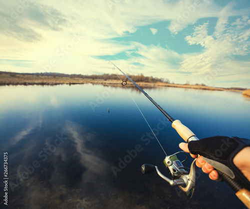 Printed kitchen splashbacks Fishing hand with spinning and reel on the summer lake