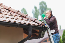 Man Repairs A Tiled Roof Of Ho...