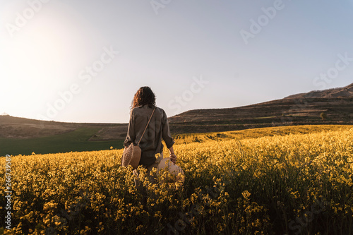 Obraz Unrecognizable woman walking among flowers - fototapety do salonu