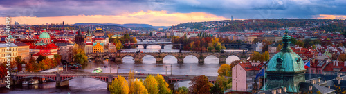 Obraz Sunset in Prague panorama, view to the historical bridges, old town and Vltava river from popular view point in the Letna park, autumn landscape in sunset light with amazing cloudy sky, Czech Republic - fototapety do salonu
