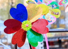 Multicolored Pinwheel Toy With Flower On Beach