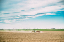 Tractor With Seeder In Dusty Field In Spring Season. Beginning Of Agricultural Spring Season