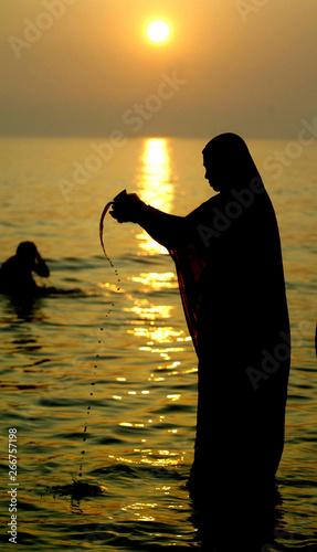 HINDU WOMAN PERFORMS EVENING PRAYER TO THE SUN GOD SURYA AT SAGAR