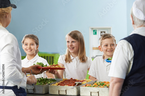 Pupils In School Cafeteria Being Served Lunch By Dinner Ladies Canvas