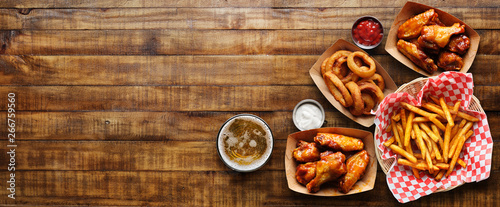Fotografija pub appetizers such as chicken wings, onion rings and french fries in panoramic