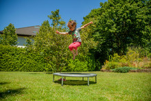 Summer Holiday Concept. Little Cute Child Girl Having Fun Outdoors And She Jumping On A Trampoline.