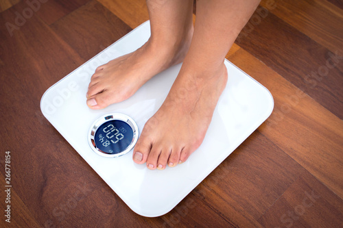 Fotografia Woman bare feet standing on a digital scale with body fat analyzer that uses bio