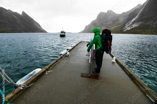Man with a backpack waiting at a jetty for the arriving ferry boat to drive from Vinstad to Reine on Lofoten in Norway