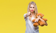 Young Beautiful Blonde Woman Holding Teddy Bear Over Isolated Background Pointing With Finger To The Camera And To You, Hand Sign, Positive And Confident Gesture From The Front