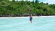 Woman holding snorkeling gear walking on sunny tropical beach caribbean sea palm trees turquoise water white sand coastline at Pulau Tailana Banyak Islands Sumatra Indonesia rear view