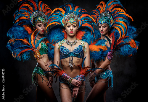 Spoed Foto op Canvas Carnaval Portrait of a group sexy dancers female in colorful sumptuous carnival feather suits. Isolated on a dark background.
