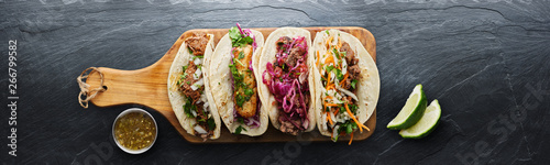 four mexican street tacos with fish barbacoa and carnitas shot in panoramic composition on top of serving wooden board - 266799582