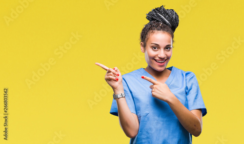 Obraz Young braided hair african american girl professional nurse over isolated background smiling and looking at the camera pointing with two hands and fingers to the side. - fototapety do salonu