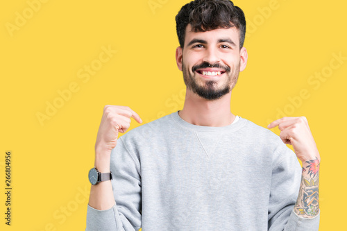 Cuadros en Lienzo Young handsome man wearing sweatshirt over isolated background looking confident with smile on face, pointing oneself with fingers proud and happy