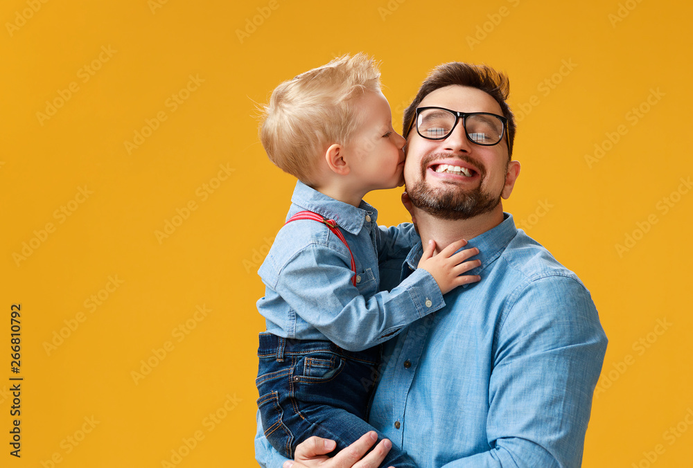 Fototapety, obrazy: happy father's day! cute dad and son hugging on yellow background.