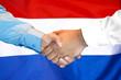 Leinwandbild Motiv Business handshake on Netherlands flag background. Men shaking hands and Dutch flag on background. Support concept