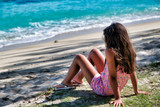 Side view of young girl sitting on the beach at water edge - 266816770