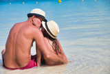 Mother and daughter talking on a beautiful beach, sitting on the water edge, view from the back, kissing each other - 266816904