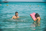Man splashing water on the sea with his daughter - 266817143