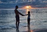 Father and daughter silhouettes at sunset on the beach - 266817331