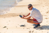 Man setting up his drone on the beach - 266817356