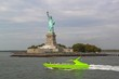 Beautiful view of green speedboat passing by famous Statue of Liberty. Liberty Island in New York Harbor in New York.