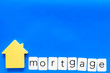 Mortgage copy for credit concept with house toy on blue background top view copy space
