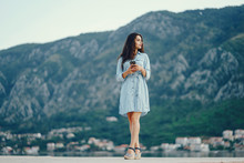 A Beautiful Young Girl In A Blue Dress Standing Near Water