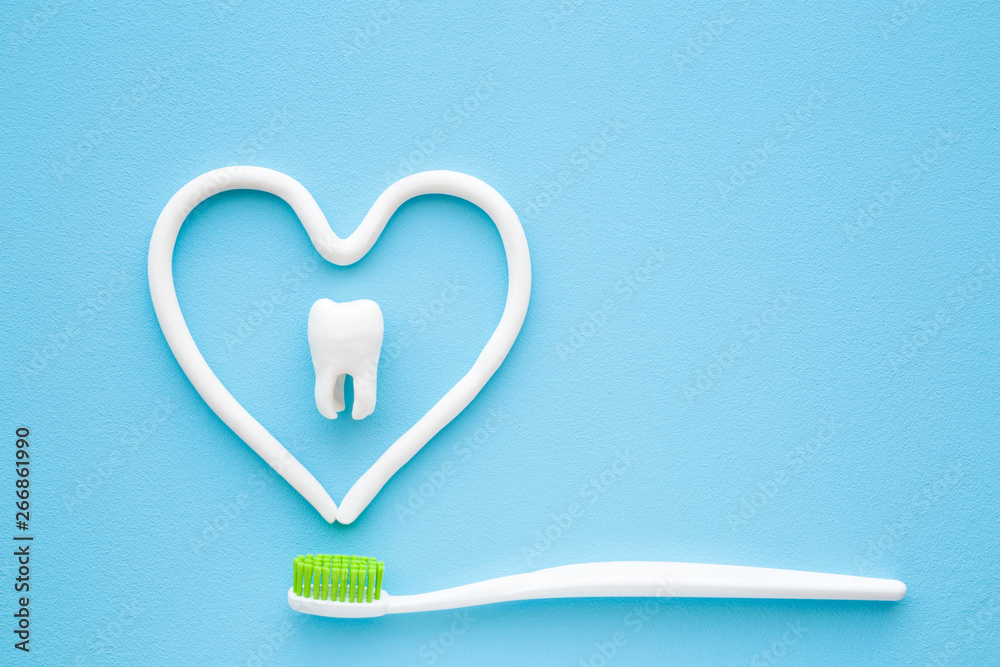 Fototapety, obrazy: Toothbrush with green bristles on pastel blue background. Heart shape created from paste. White tooth in middle of heart. Love healthy teeth. Empty place for text, quote, sayings or logo. Closeup.