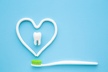Toothbrush With Green Bristles On Pastel Blue Background. Heart Shape Created From Paste. White Tooth In Middle Of Heart. Love Healthy Teeth. Empty Place For Text, Quote, Sayings Or Logo. Closeup.
