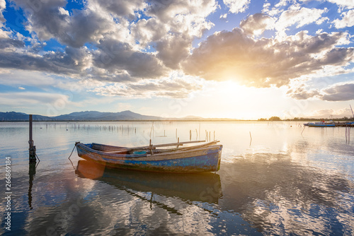 Foto op Plexiglas Schip Fisherman boat moored in the lagoon with perfect water reflection of the sunset.