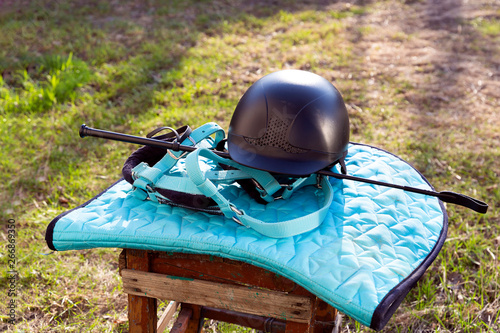 Valokuva Equipment for horse riding outdoors: bridle, whip, helmet, bandages
