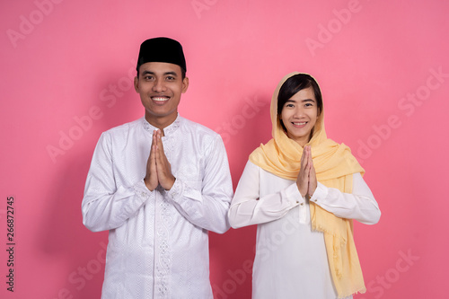 Leinwand Poster  man and woman muslim greeting on studio smiling to camera