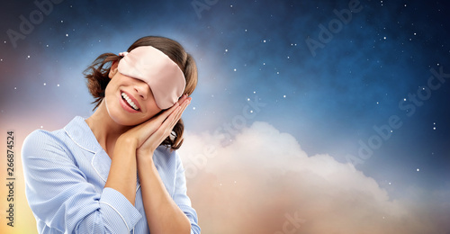 people and bedtime concept - happy young woman in pajama and eye sleeping mask over starry night sky and cloud background