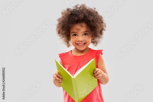 Photo  childhood, literature and people concept - happy little african american girl re