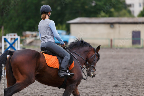 Foto Young girl riding bay horse on equestrian sport training