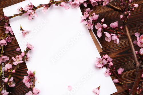 White paper sheet and sprigs of the apricot tree with flowers on wooden background. Place for text. The concept of spring came, happy easter, mother's day.Top view.Flay lay. Copy space.