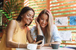 canvas print picture - Two cheerful young girlfriends sitting at the cafe indoors