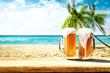 canvas print picture - Summer background of wooden desk and cold beer. Free space for your decoration. Beach landscape with palms and ocean. Summer sunny day with sun light. Beach party and summer time.